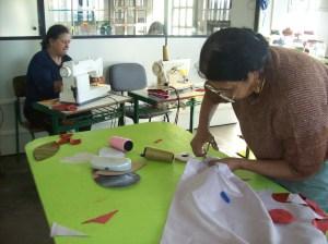 A aluna Sueli Maria Vedor (ao fundo) e a professora Rosa. São apenas três máquinas de costura para as aulas de confecção de tapetes e bonecas.